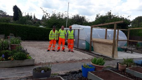 Three people in high vis work clothes standing in the Dorothy Parkes community allotment.