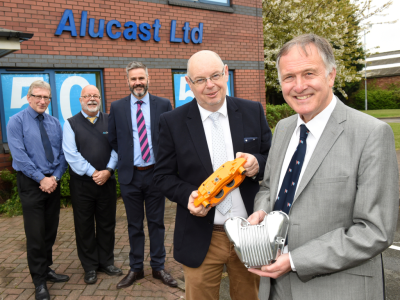 Five men in suits standing outside a brick building with corporate signage saying 'Alucast Ltd'