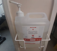 A large pump action container of alcohol hand gel attached to a wall