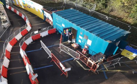 Mollies Café catering unit in what looks like a blue shipping container on a construction site with red and white barriers outside it.