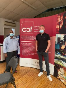 Paul of KMB with Soyfur from Community Connect Foundation both wearing masks, standing in front of a CCF banner