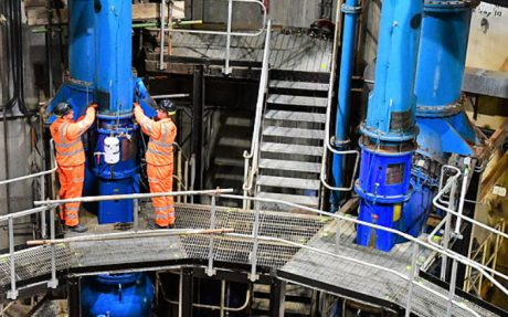 Two workmen in fluorescent orange PPE suits and hard hats working on a platform in water cleaning site