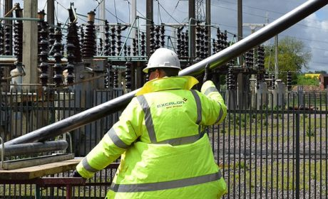 Workman wearing a hard hat and fluorescent yellow coat in front of some electricity pylons