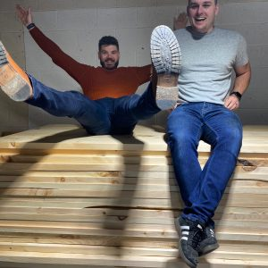 Sam Moseley and Rhys York of Grain and Frame sitting on a pile of wood