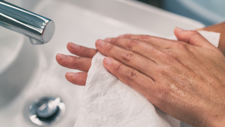 Medium to dark skin tone slim hands being washed with a cloth in a sink