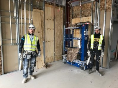 Two apprentices wearing hard hats, work boots and high vis jackets on a construction site