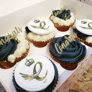 """A box of six cupcakes topped with blue and white icing and gold decorations saying """"Congrats"""""""