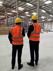 Two people wearing suits with orange high-vis vests over the top and yellow hard hats standing in a large warehouse space with their backs to the camera.