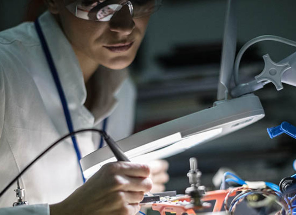 A close up of a scientist wearing protective goggles working in a lab