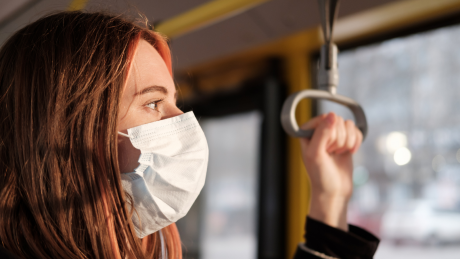Young woman in a face mask holding a grab rail on a bus