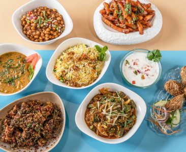 Bowls of different curries and rice and other Indian dishes on a table