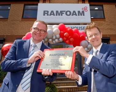 Two men in dark blue suits holding a commemorative plaque in front of a red and white balloon arch outside a building. The building says 'Ramfoam' and the plaque says 'Enterprise House officially opened by Andy Street, Mayor of the West Midlands, 29.07.2021'