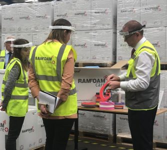 Three people wearing yellow high-vis vests and plastic visor face masks standing infront of a large pile of boxes.