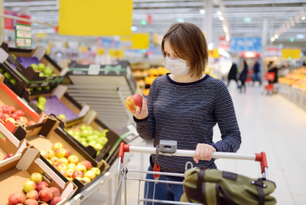Young woman with a trolley in the produce section of a supermarket, wearing a face covering
