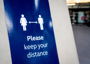 """A blue sign with the text """"Please keep your distance"""" and a male and female symbol in white with an arrow in between them"""