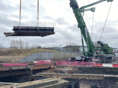A green crane lifting up part of a metal bridge.