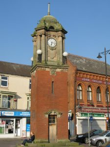 A clock tower with buildings behind it.