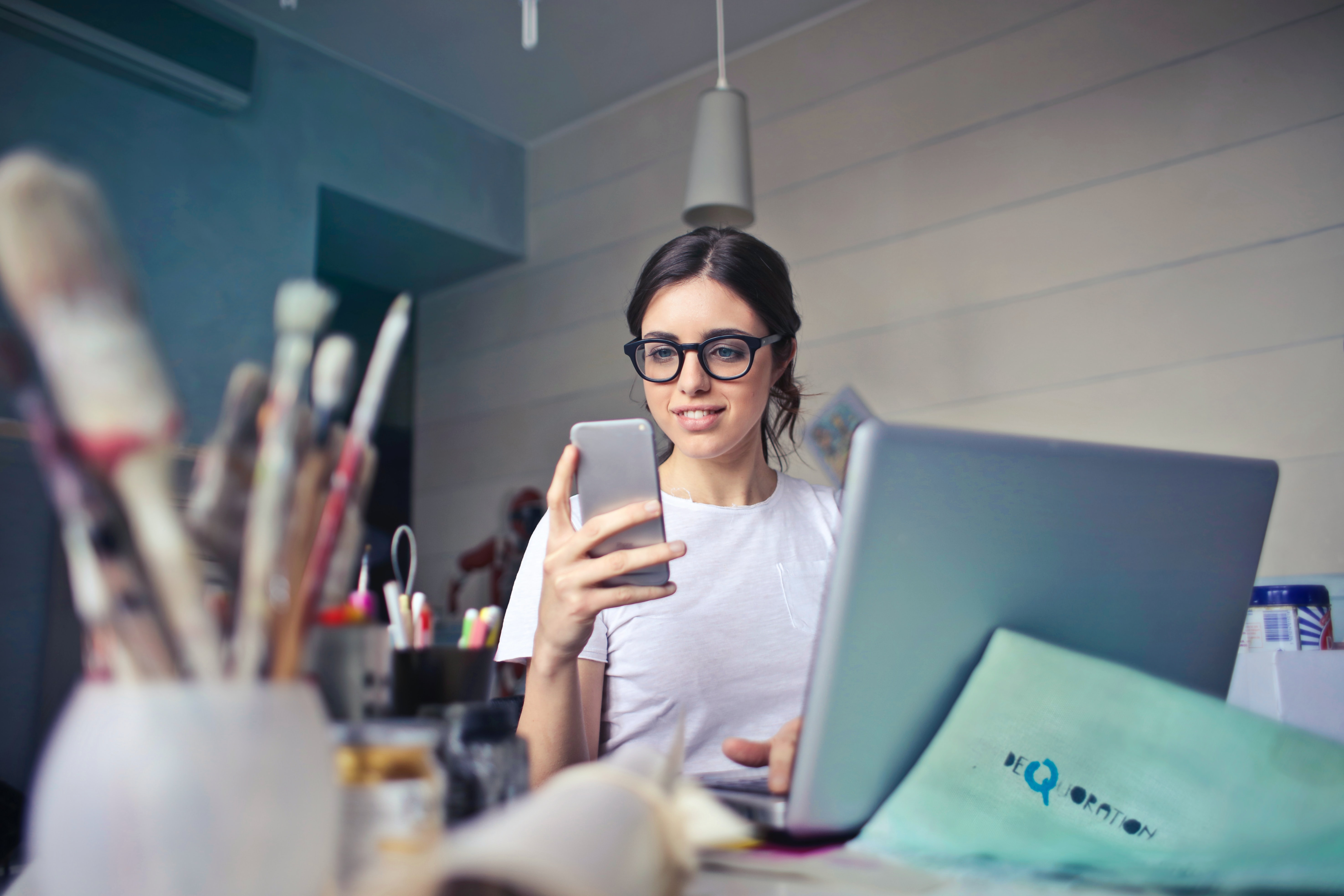 A young woman wearing glasses sitting at a laptop holding a mobile phone in front of her, with a pot of paint brushes out of focus in the corner of the foreground