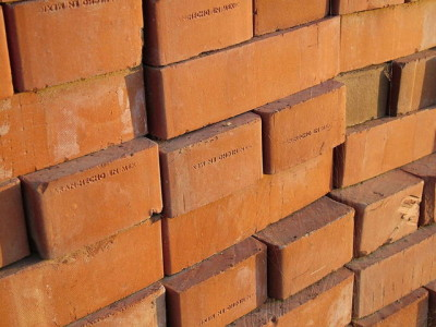 Close up image of a pile stacked red bricks