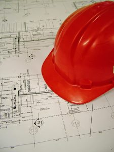 A red hard hat on an architect's drawing