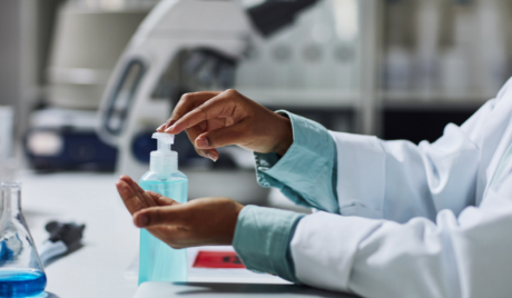A close-up of a woman's hands - slim, brown skin, wearing a lab coat or overalls - applying hand sanitiser at a workstation