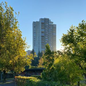 A tall building in the background behind some green trees in the foreground