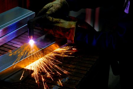 Close up of the gloved hands of a steel worker using a blow torch creating sparks on metal