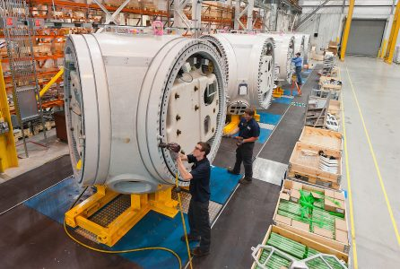 Three people working in a large factory setting.